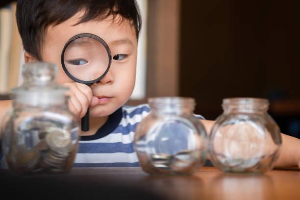 niedlichen Jungen mit einer Vergrößerung, um Geldmünzen in Glas zu finden, Geld sparen Konzept – Foto