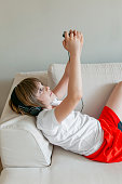 Cute boy playing game with his mobile phone at home