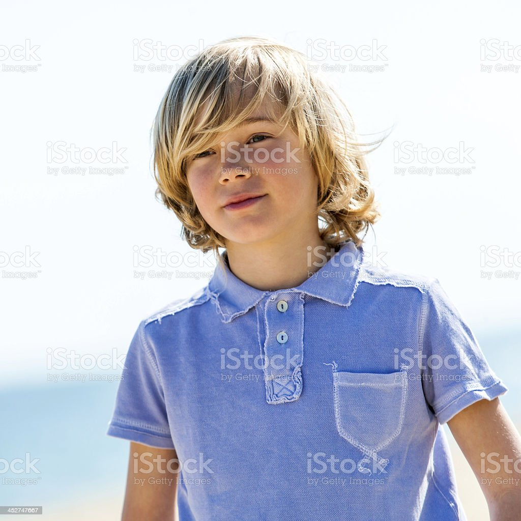 Cute boy with blue polo shirt outdoors. royalty-free stock photo