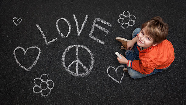 cute boy, with chalk on street/tarmac, love peace flowers happin - symbols of peace stock photos and pictures