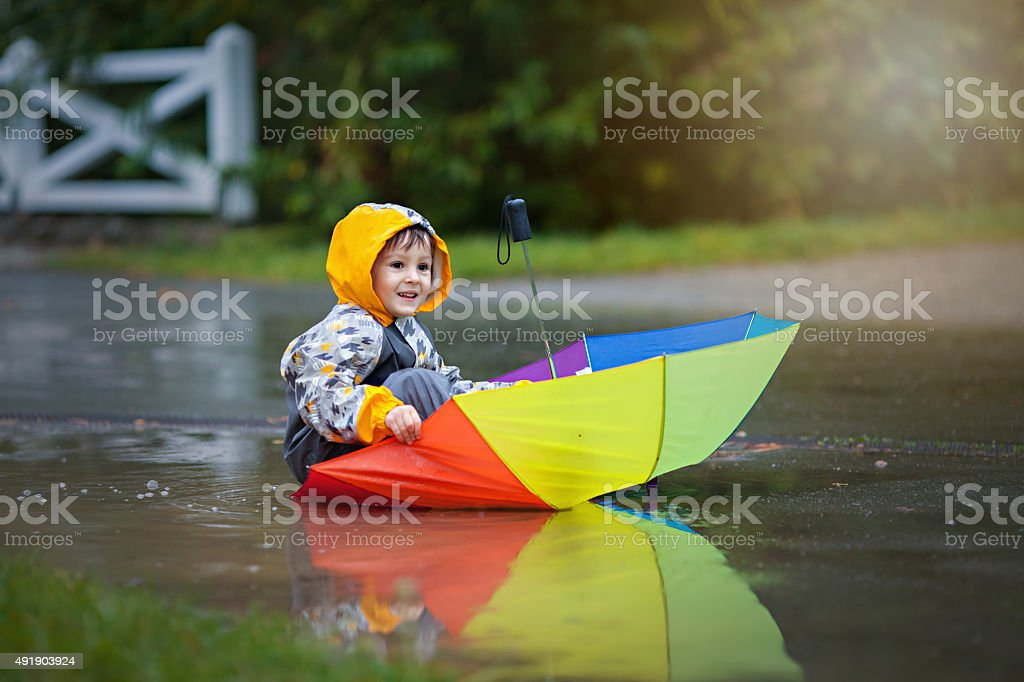 Cute boy with colorful rainbow umbrella on rainy day stock photo
