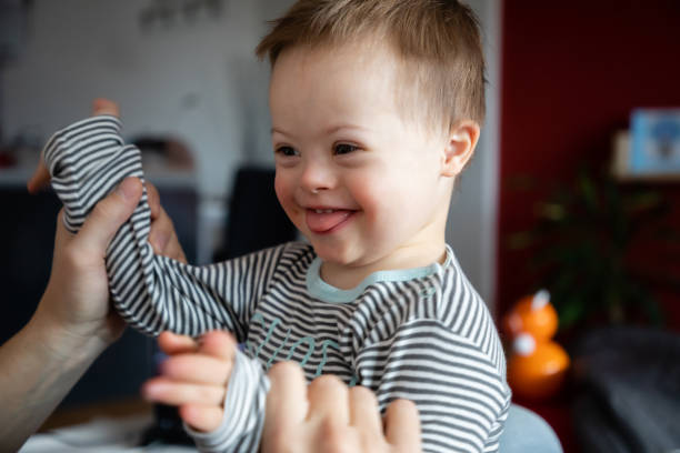 Cute boy with Down syndrome playing with dad on in home Cute boy with Down syndrome playing with dad on in home living room baby human age stock pictures, royalty-free photos & images