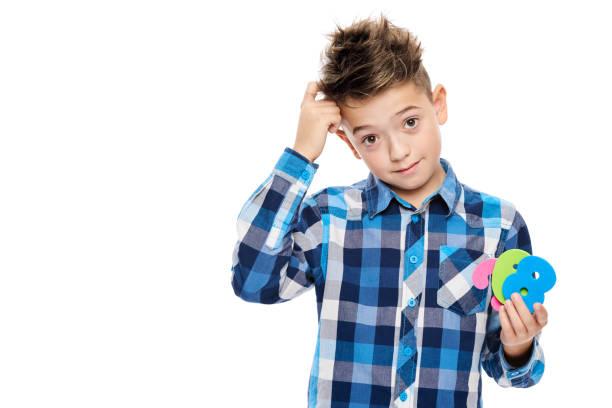 Netter Junge mit Dyskalkulie halten große bunte Zahlen und kratzte sich am Kopf. Lernbehinderung-Konzept auf weißem Hintergrund. – Foto