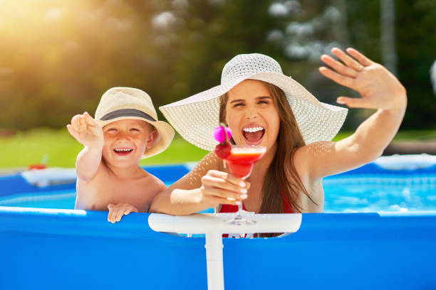 Sevimli çocuk ile onun anne oyun içinde yüzme havuz sırasında yaz stok fotoğrafı