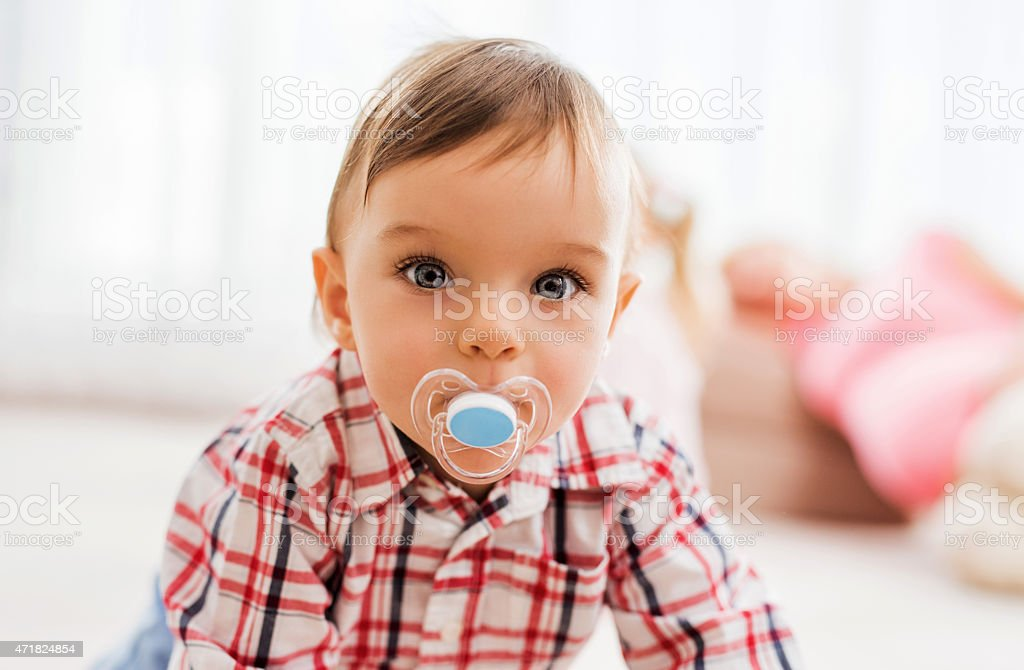Cute boy with pacifier looking at the camera. stock photo