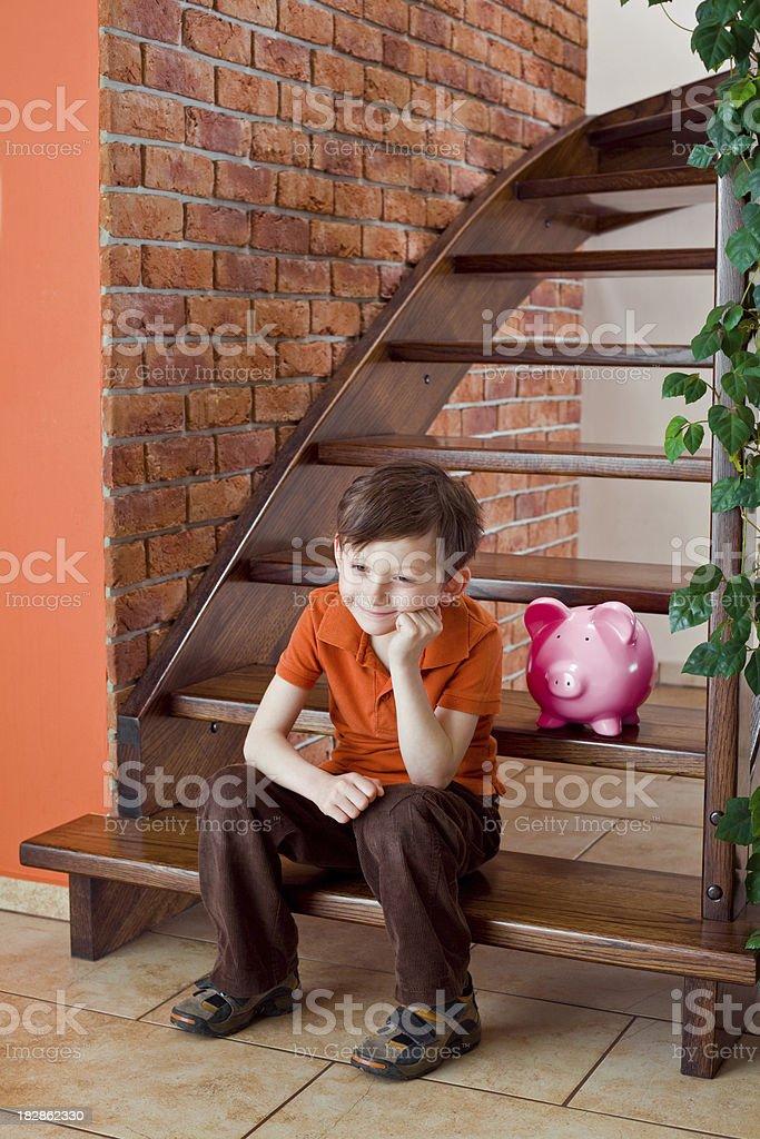 Cute boy with piggy bank royalty-free stock photo