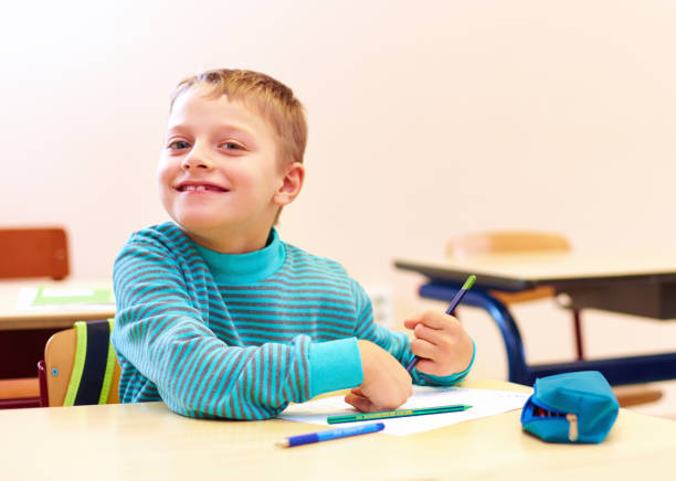 cute boy with special needs writing letters while sitting at the desk in class room cute boy with special needs writing letters while sitting at the desk in class room autism stock pictures, royalty-free photos & images