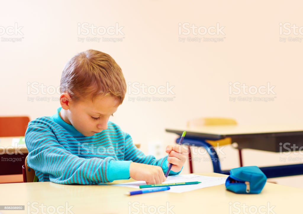 cute boy with special needs writing letters while sitting at the desk in class room - foto stock
