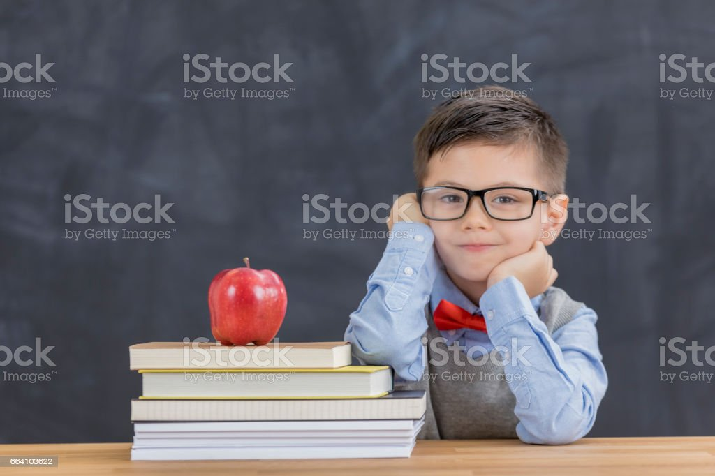 Cute boy with stack of books in the classroom stock photo