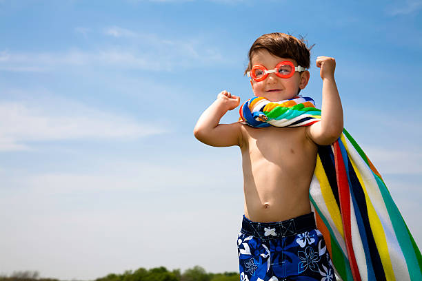 Cute Boy With Swimwear On Flexing Muscles  swimming goggles stock pictures, royalty-free photos & images
