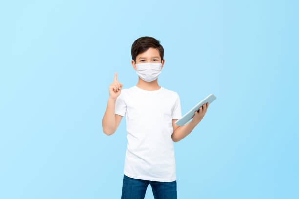 Cute boy with tablet computer wearing medical mask to protect from germs and viruses stock photo