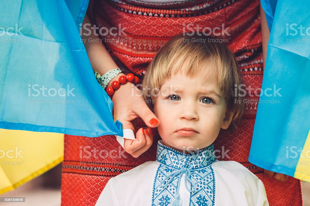Cute boy with the national flag of Ukraine stock photo