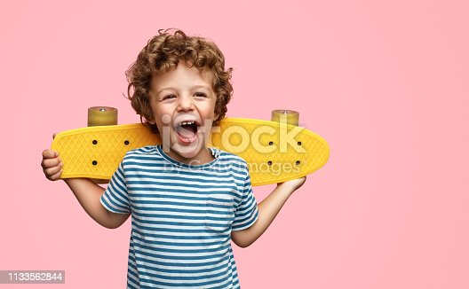 istock Cute boy with yellow skateboard 1133562844