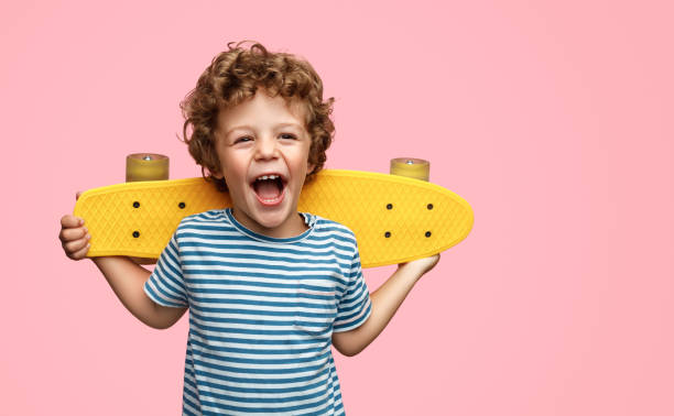 Cute boy with yellow skateboard Funny little boy holding yellow skateboard on shoulders and screaming while standing on pink background leisure equipment stock pictures, royalty-free photos & images
