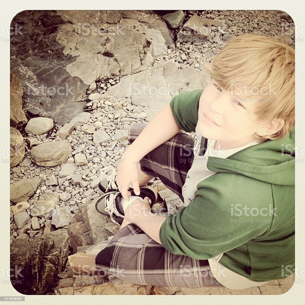 Cute Boy, Young Teen Sitting on Rocks royalty-free stock photo