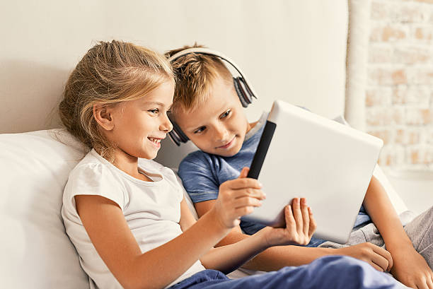 cute brother and sister enjoying tablet at home - ゲーム ヘッドフォン ストックフォトと画像