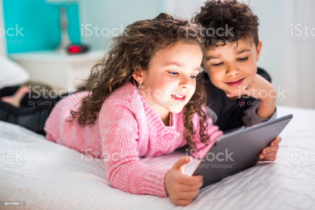Cute Brother And Sister Enjoying Tablet At Home Stock Photo More