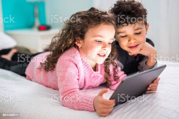 Cute brother and sister enjoying tablet at home picture id854469512?b=1&k=6&m=854469512&s=612x612&h=ahvtmgub7edzgb4a0zjedrcaqcxarrxsf9ir8h9pi 4=