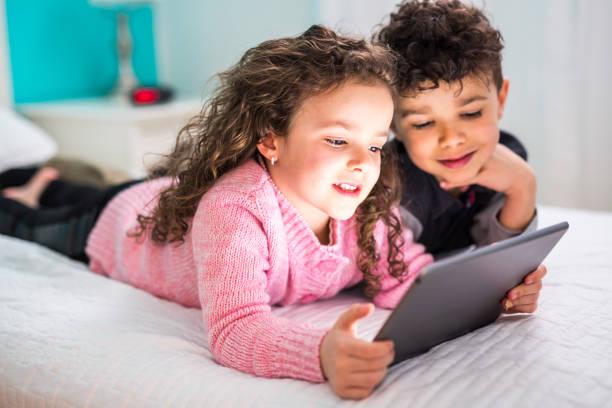 Bonito irmão e irmã apreciando o tablet em casa - foto de acervo
