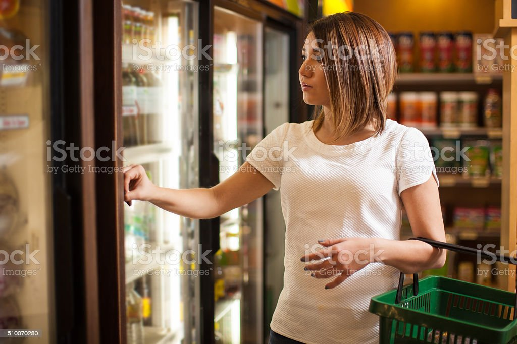Cute brunette buying some groceries stock photo