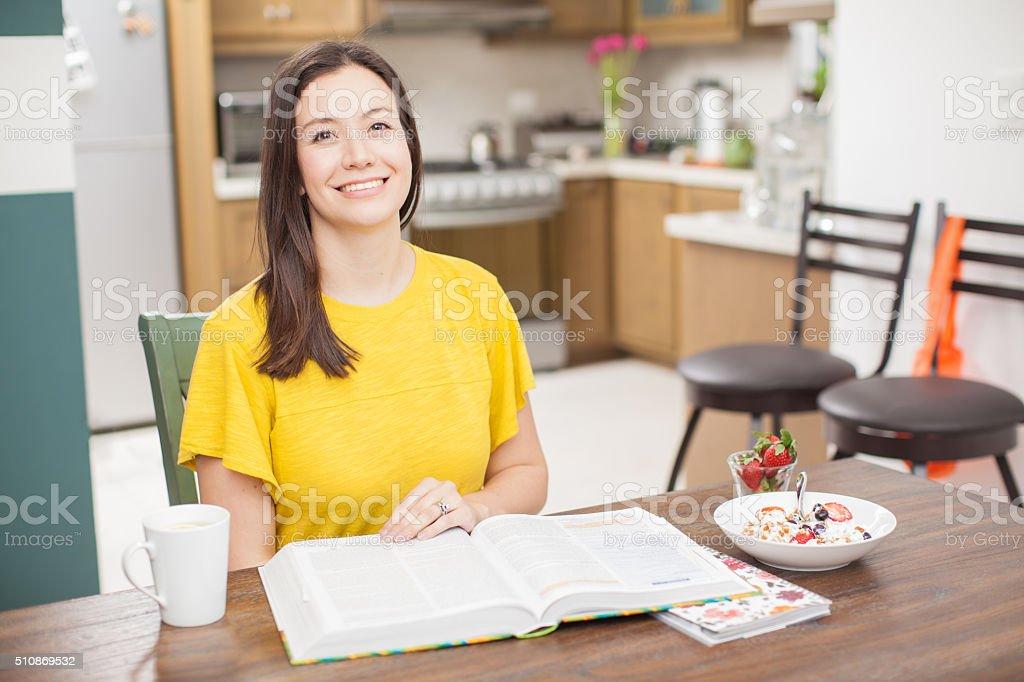 Cute brunette enjoying breakfast at home stock photo