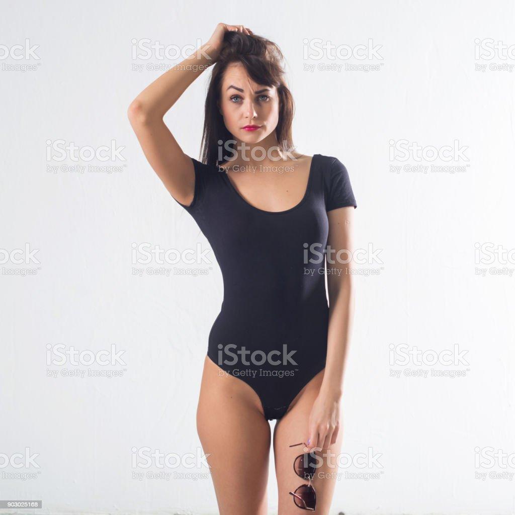 Cute brunette female model posing, wearing black one piece underwear suit, touching her hair stock photo