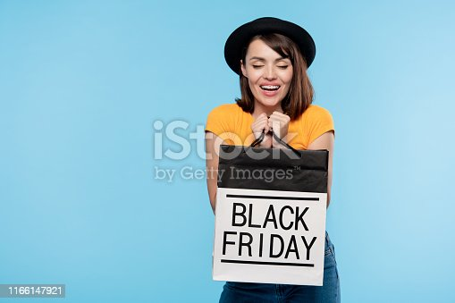 istock Cute brunette girl in hat and t-shirt holding black friday paperbag 1166147921
