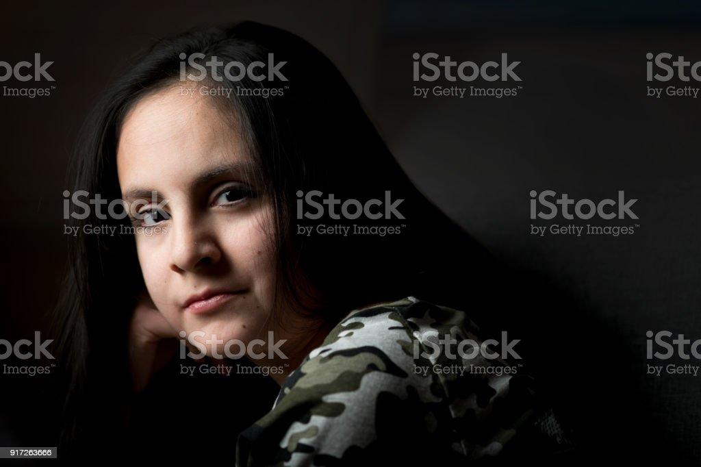 Cute brunette girl posing in low key stock photo