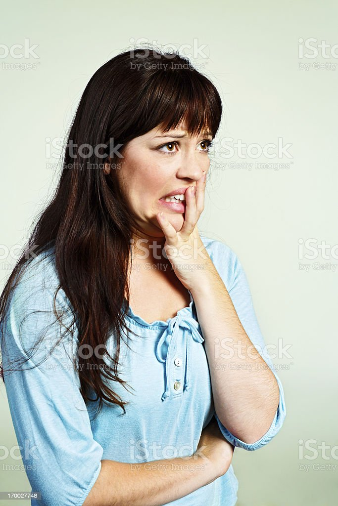Cute brunette grimaces at something, hand to her face royalty-free stock photo