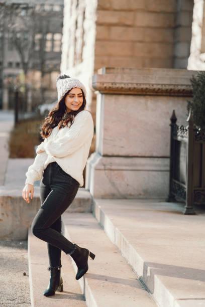 Cute brunette in a white sweater in a city stock photo