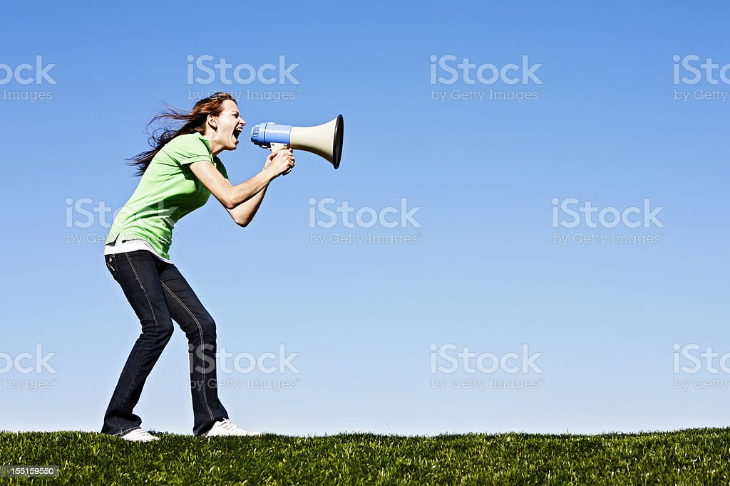 Cute brunette shouts into loud hailer in field royalty-free stock photo