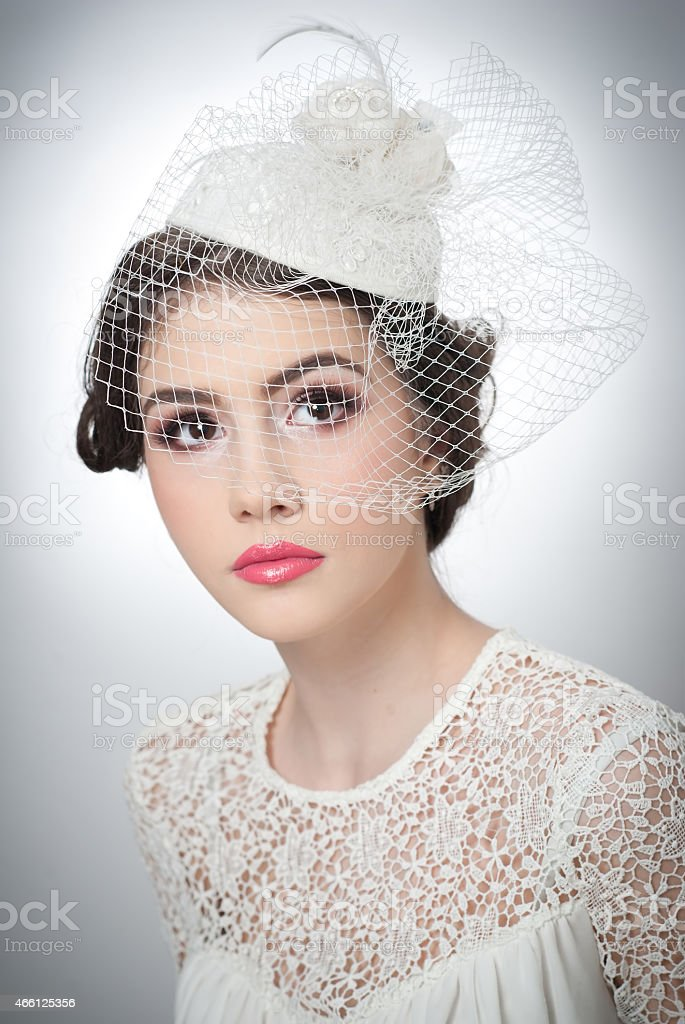 Cute brunette with white cap and veil, studio shot stock photo