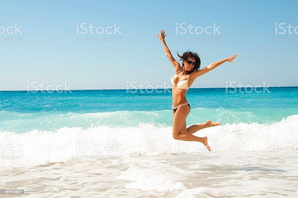 Симпатичная брюнетка женщина, прыжки на море стоковое фото