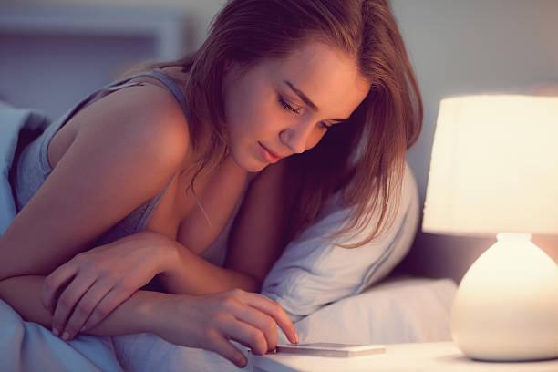 sexy brunette frau liegt auf ihrem bett, mit smartphone - nachttischleuchte touch stock-fotos und bilder