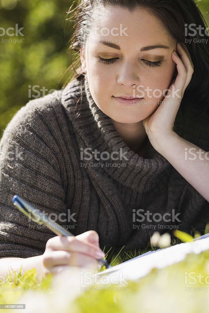 Cute brunette writing lying on the grass royalty-free stock photo