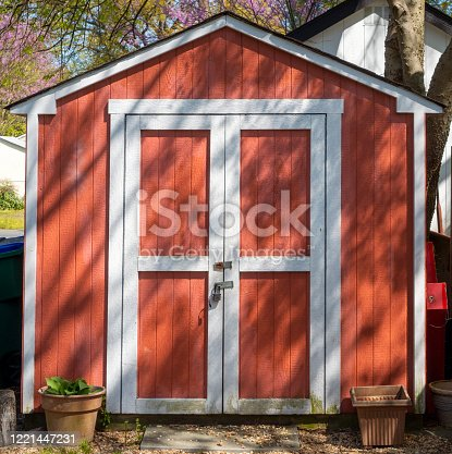 Cute burnt orange utility tool shed with tree shadows.