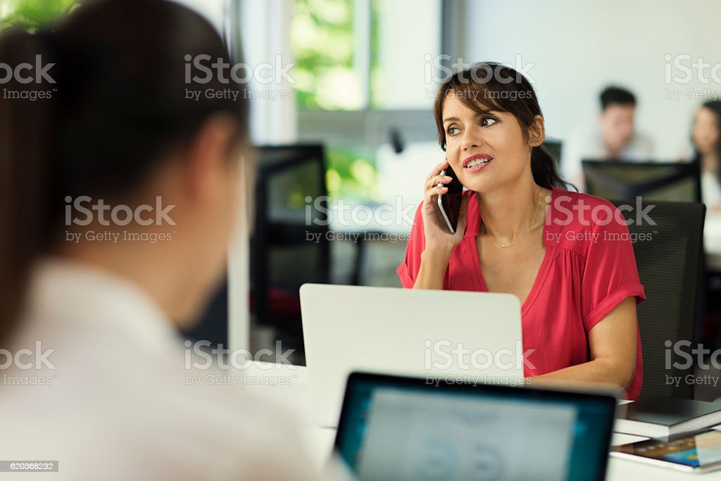 Cute business woman on mobile phone in coworking office startup foto de stock royalty-free
