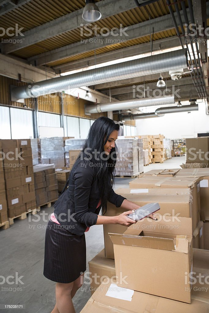 Cute businesswoman cheching paper boxes in a warehouse royalty-free stock photo