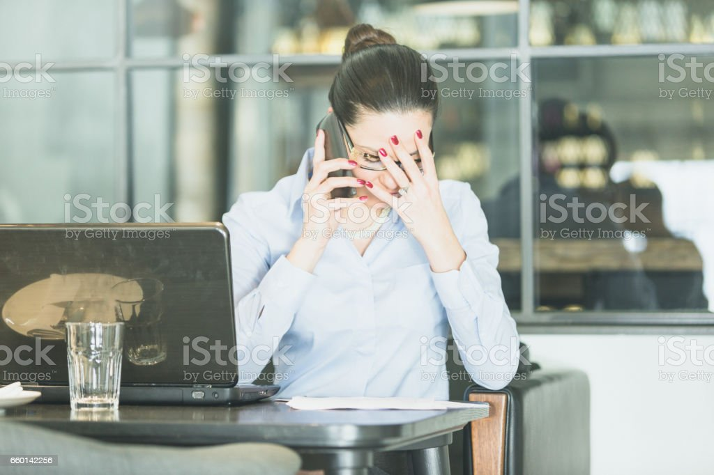 Cute businisswoman with eyeglases, working on laptop, browsing some papers, talking to mobile phone stock photo