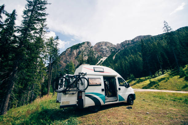 Cute camper van RV in wild camping spot in nature stock photo
