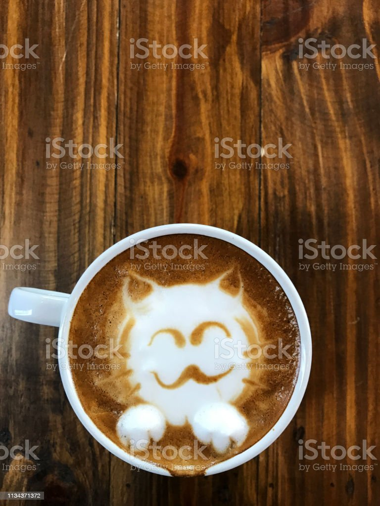 Cute cat face latte art coffee in white cup on wooden table ; love...