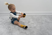 Cute caucasian baby girl learning to put on socks at home, on floor, white wall behind. Casual wear, indoors.