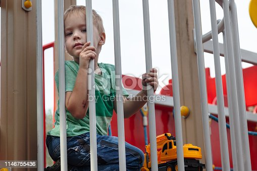 Cute caucasian blond baby boy sits under the fence of children playground. Cute, serious and humile expression on the face, strong emotions of loneliness. Outdoor, copy space, yellow toy (grader).