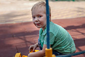 Cute caucasian blond baby boy with blue eyes sits on the cover of children playground with a toy, yellow excavator.
