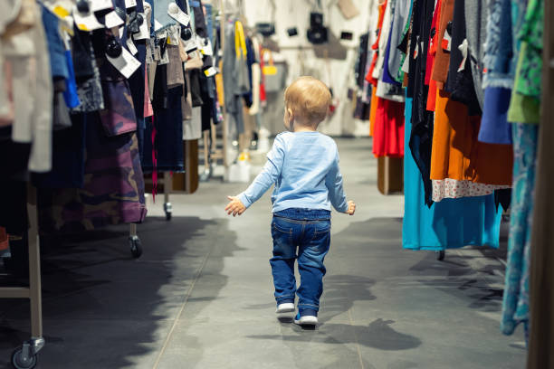 cute caucasian blond toddler boy walking alone at clothes retail store between rack with hangers. baby discovers adult shopping world. baby get lost at big hypermarket shopping mall - lost стоковые фото и изображения