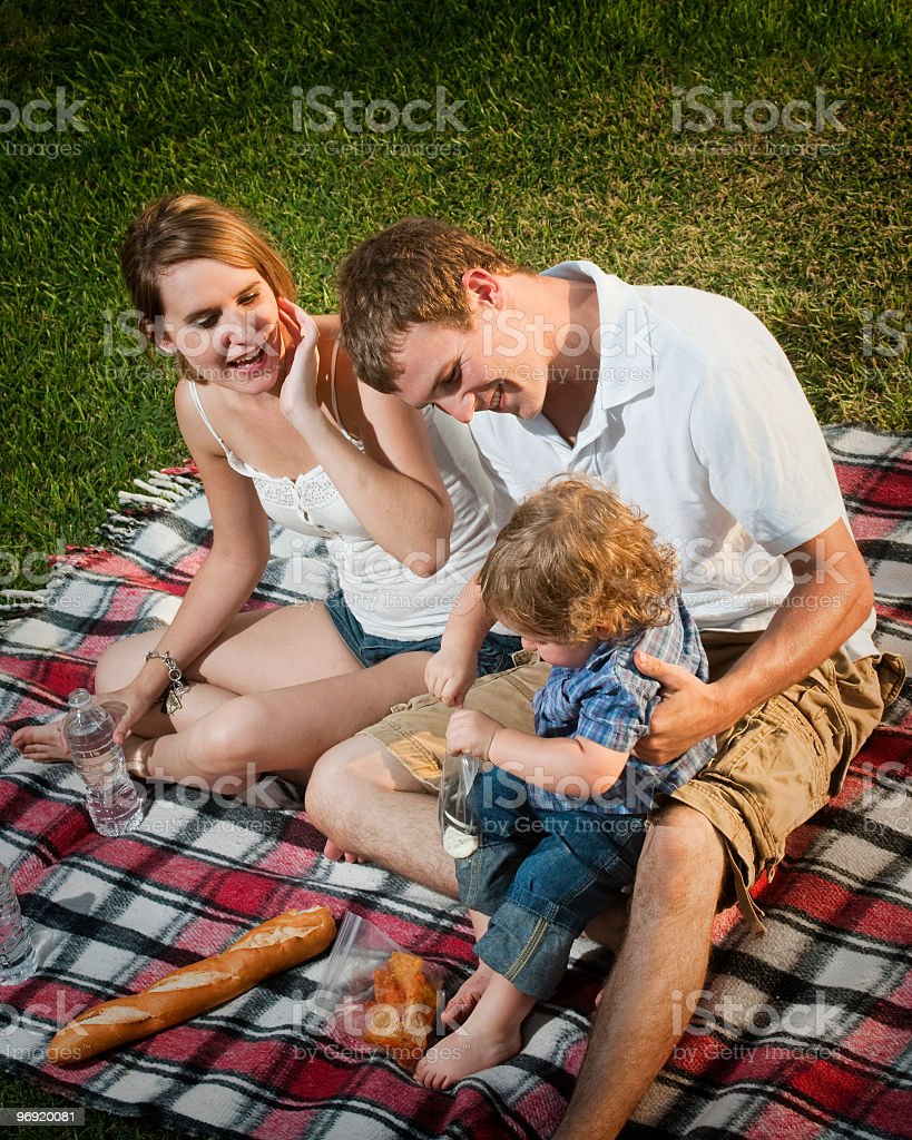Cute Caucasian family of three having afternoon picnic royalty-free stock photo