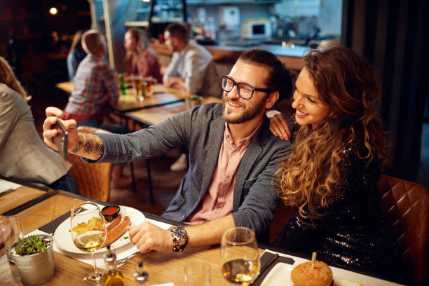 Cute caucasian fashionable couple sitting in restaurant at dinner and taking selfie. stock photo