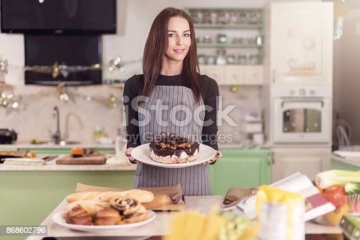 istock Cute Caucasian female baker showing cakes, cookies and other pastry made in bakery 868602796