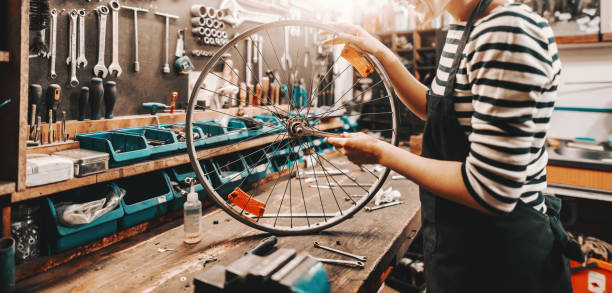 Cute Caucasian female worker holding and repairing bicycle wheel while standing in bicycle workshop. Cute Caucasian female worker holding and repairing bicycle wheel while standing in bicycle workshop. bicycle shop stock pictures, royalty-free photos & images