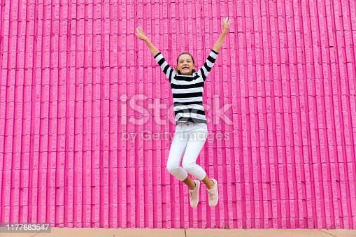 Cute caucasian girls celebrating her 13th birthday becoming a teenager in front of a hot pink wall outside by jumping up with joy